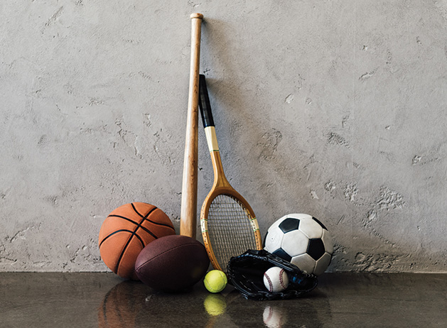 A variety of sports equipment: basketball, football, baseball bat, ball and glove, tennis racket, soccer ball