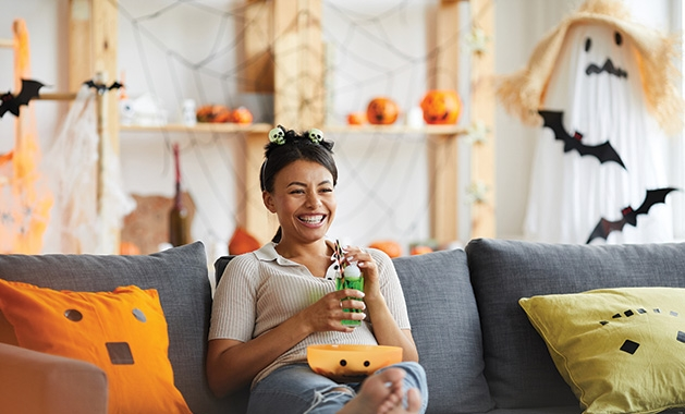 A woman sits on a couch watching scary TV shows.