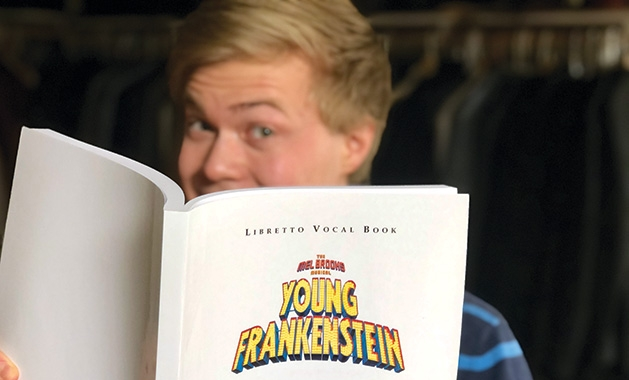 """A member of Woodbury Community Theatre holds the program for """"Young Frankenstein."""""""