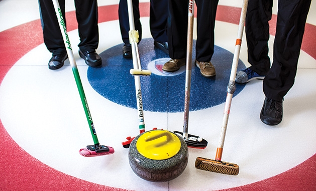 Four curling brooms and a stone at the St. Croix Curling Center