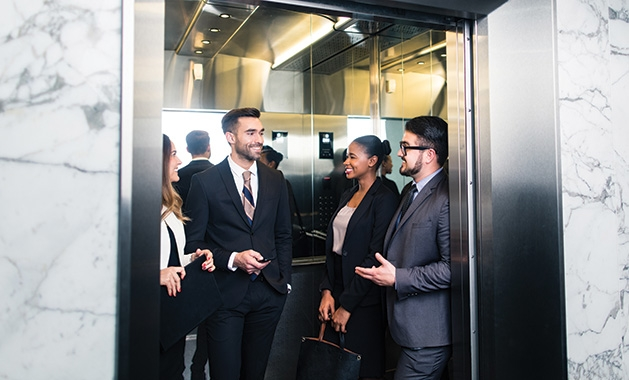 A group of people ride on an elevator.