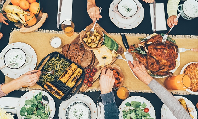A family gathers around a table for Thanksgiving dinner