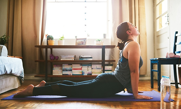 A woman does yoga in her living room.