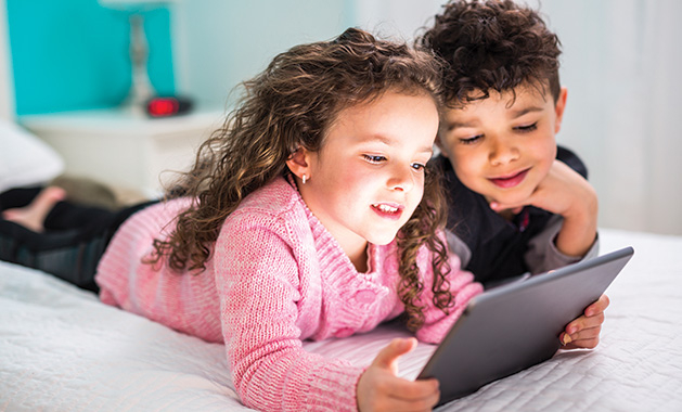 Two children look at a tablet during their screen time.