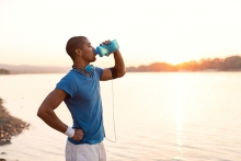 A man drinks water on a sunny morning.