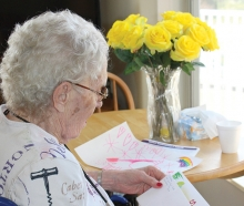 A senior at Woodbury Senior Living reads a handwritten holiday letter.