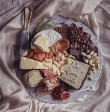 A Valentine's Day platter featuring, cheese, chocolate and other snacks.