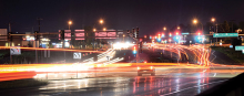 A long exposure photograph shows the city lights and cars on Radio Drive in Woodbury.