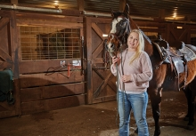 Erin Olsen poses with a horse at True North Ranch