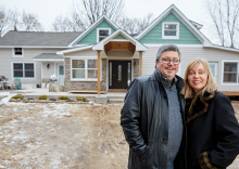 Al Shams and wife Debra stand in front of a renovated 1880 Woodbury farmhouse.