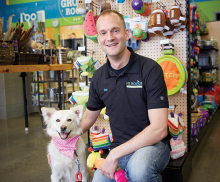 Rian Thiele, co-owner of Pet Evolution in Woodbury and Arden Hills, poses with a dog.