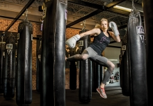 Sarah Krotz, a coach at TITLE Boxing Club Woodbury, kicks a punching bag.