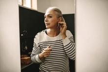 A woman tries on earrings in a mirror.