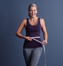 A woman measures her waist to hip measurement to track her fitness.