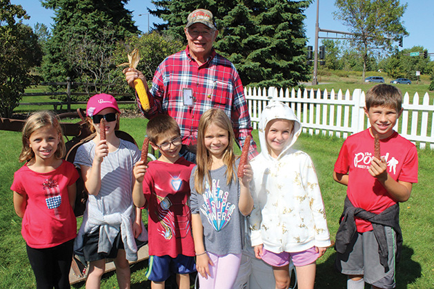 Children hold up corn at the Woodbury Heritage House