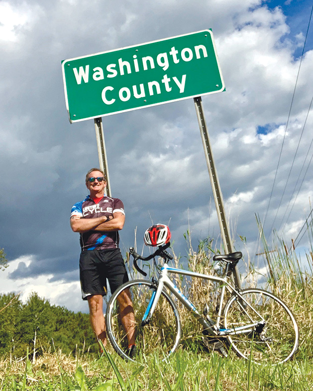 Terry Stille stands with his bike near a Washington County road sign.