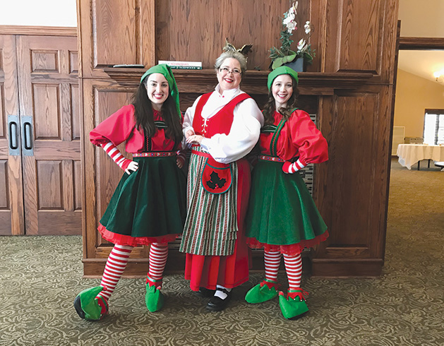Three women clad in Christmas attire pose for a photo at the HealthEast Sports Center Holiday Exhibition and Party